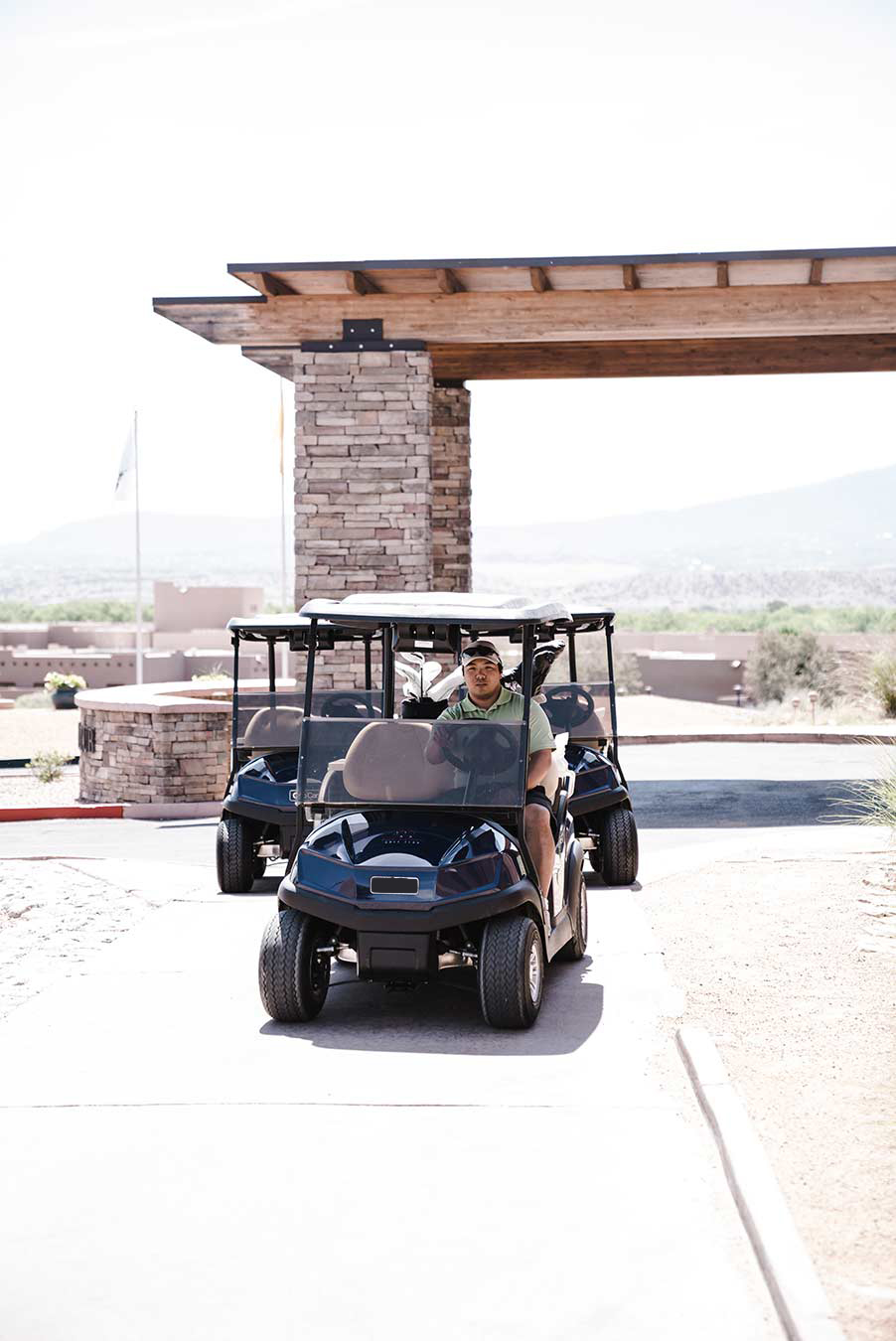 golf carts driving out of a country club